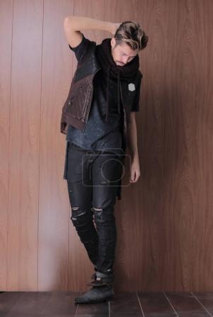 Photo pour Gros plan image d'un beau jeune homme de la mode tenant une main à travers les cheveux, regardant la caméra . - image libre de droit