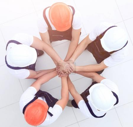group of construction workers with hands clasped together