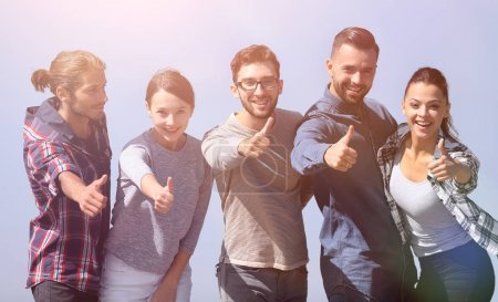Photo for Smiling group of young people showing thumb up.isolated on a blue background - Royalty Free Image