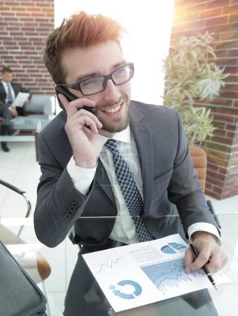 businessman talking on smartphone at his Desk