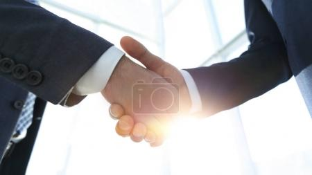 Two  business men going to make handshake