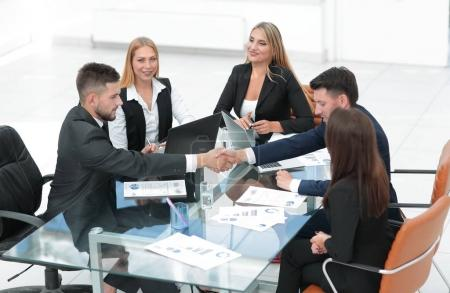handshake of business partners sitting at your Desk