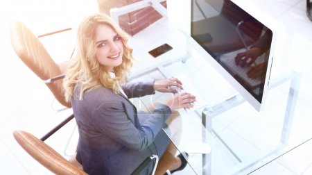 business woman sitting at her Desk and looking at camera