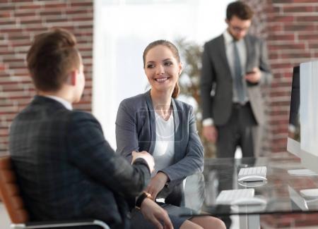 Photo pour Handshake Manager et client assis au bureau - image libre de droit