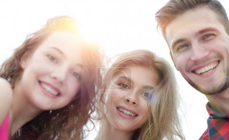 Foto de Primer plano de tres jóvenes felices sonriendo sobre fondo blanco - Imagen libre de derechos