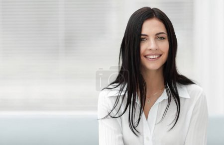 successful young woman sitting at a desk on a blurred background.