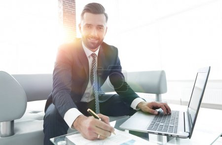 Businessman working with business graphics on a laptop computer