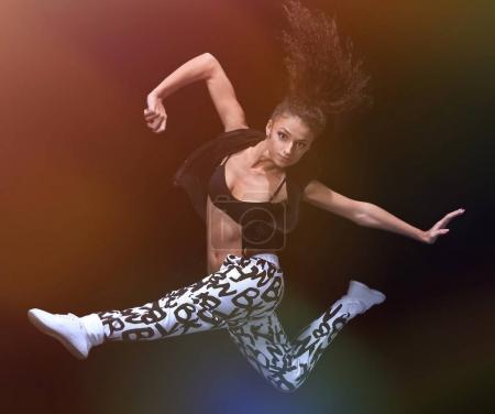 Photo pour Jeune femme assez moderne style hip-hop mince, saut de fond de studio danse et isolé - image libre de droit