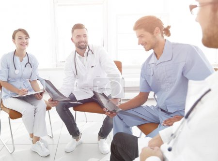 doctors discuss an x-ray ,sitting in the office.