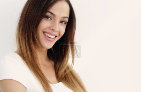 Photo for Beautiful smiling woman with clean skin, natural make-up, and white teeth on grey background - Royalty Free Image