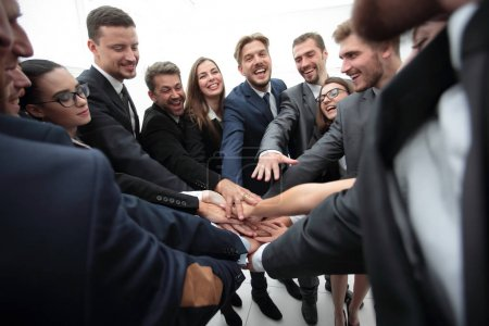 large group of business people standing with folded hands together
