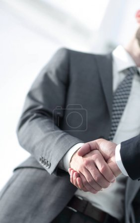 Friendly smiling businessmen handshaking. Business concept photo