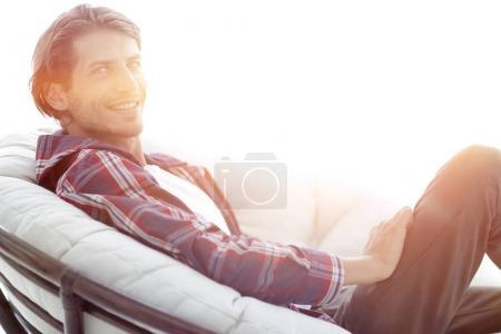 Photo pour Gars réussi assis dans une grande chaise ronde confortable. vue latérale de la photo a un espace vide pour le texte - image libre de droit