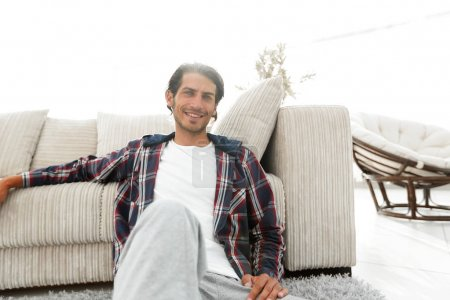 Photo for Confident guy sitting on the carpet in a cozy living room. concept of buying a home - Royalty Free Image