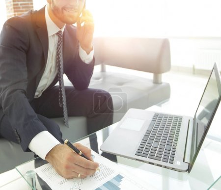 Businessman talking on smartphone about financial charts.