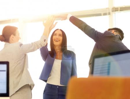 Photo for Happy business team giving high five in office - Royalty Free Image