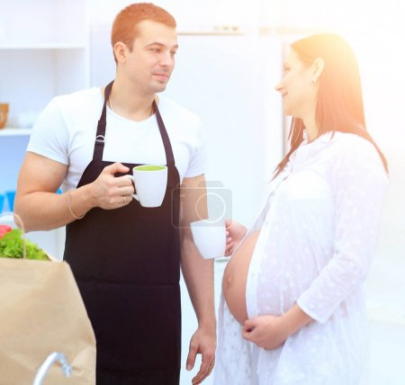 husband and his pregnant wife with a Cup of cocoa standing in th