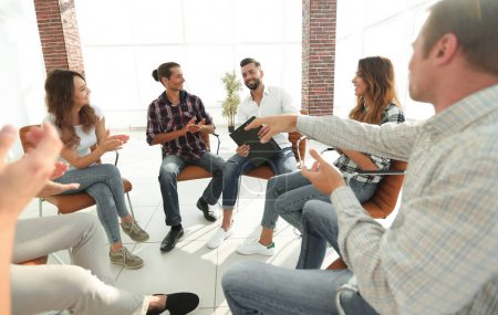 Photo for Business people are applauding and smiling while sitting in circle in office - Royalty Free Image