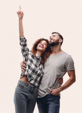 oung couple looking up and pointing upwards