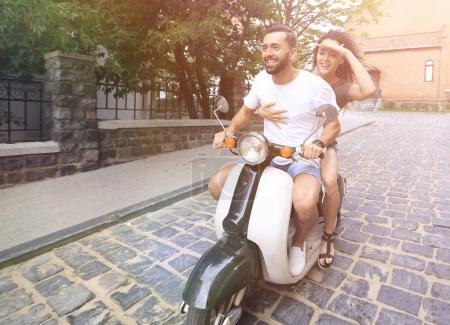 Photo pour Heureux jeune couple s'amuser sur un scooter - image libre de droit