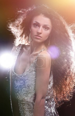 Young dancing woman, with flashes on background