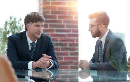 Photo pour Deux hommes d'affaires discutent de tâches assis à une table. Concept d'entreprise - image libre de droit