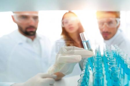 background image is a group of scientists studying the liquid in the glass tube.
