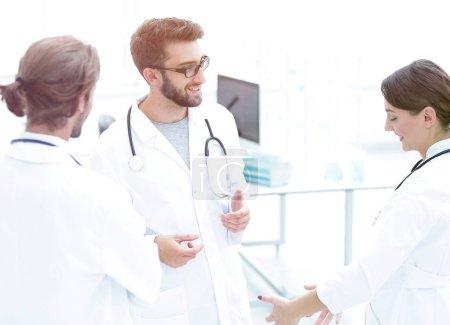 Photo pour Groupe de médecins impliqués dans une discussion sérieuse avec les dossiers médicaux - image libre de droit