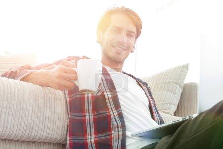 Photo pour Homme avec ordinateur portable tenant une tasse assise sur le sol près du canapé dans un salon moderne - image libre de droit