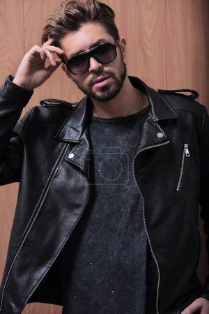Photo pour Homme élégant attrayant avec barbe en veste en cuir et lunettes de soleil regardant la caméra - image libre de droit