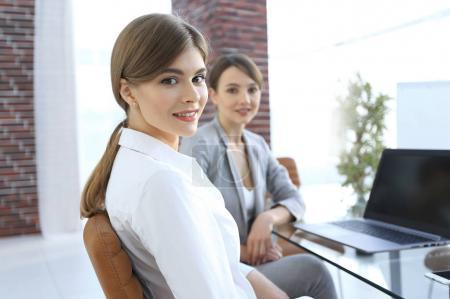 Photo pour Deux employés de bureau assis derrière un bureau. vie de bureau - image libre de droit