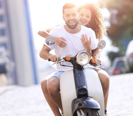 Photo for Young happy couple riding scooter together  smiling - Royalty Free Image