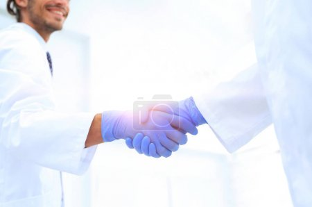 Man doctor shakes hand with another doctor in hospital
