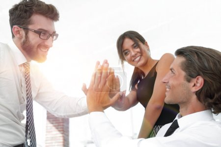 members of the business team give each other high five
