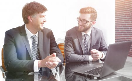 Photo for Portrait of two business people sitting at office desk in office - Royalty Free Image