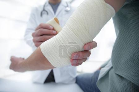 Orthopedist applying bandage onto patients hand in clinic
