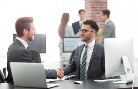 Photo for Two managers in suits shaking hands at business meeting in office - Royalty Free Image