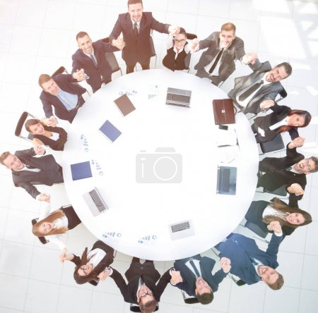 Photo for View from the top. Director and business team sitting at the round table and holding each others hands. the business concept. - Royalty Free Image