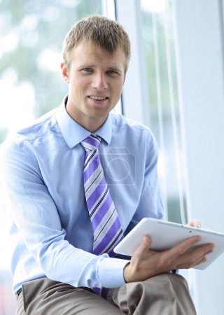 Handsome young man in a blue shirt using a tablet