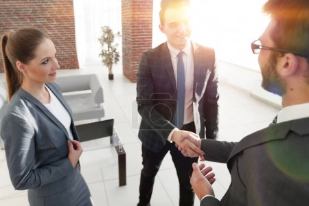 Photo for Female assistant looks at the handshake business partners - Royalty Free Image