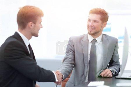 Photo pour Poignée de main de partenaires d'affaires assis à un bureau. concept de partenariat - image libre de droit