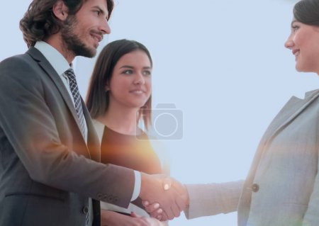Photo for Business partners handshaking over business objects on workplace - Royalty Free Image