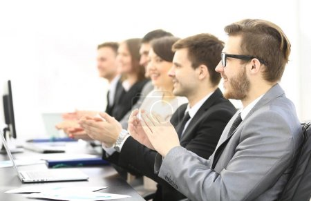 Photo for Business team applauding the speaker sitting behind a Desk - Royalty Free Image