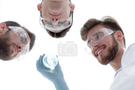 closeup.a group of scientists looks at the liquid in the beaker