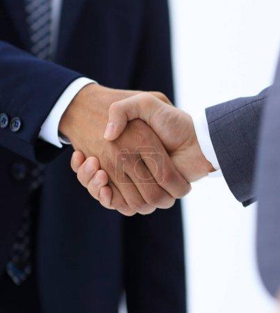 Photo pour Deux jeunes hommes d'affaires debout en face l'un de l'autre et serrent la main . - image libre de droit
