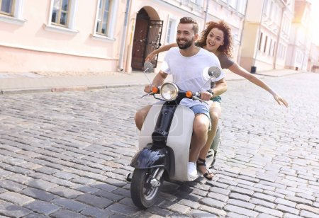 Photo for Happy cheerful couple riding vintage scooter outdoors. - Royalty Free Image