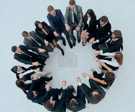Photo for Concept of team building.large business team sitting in a circle and holding each others hands - Royalty Free Image