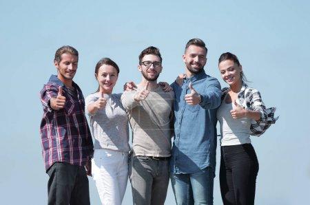 Foto de Grupo de jóvenes mostrando el pulgar hacia arriba.aislados sobre un fondo azul - Imagen libre de derechos