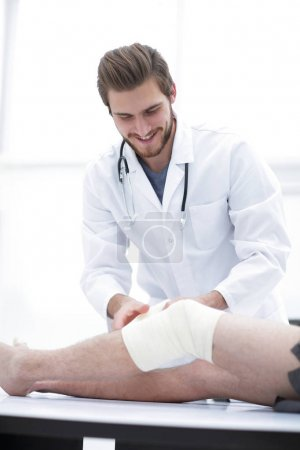 smiling doctor looking at the bandage on the patients leg