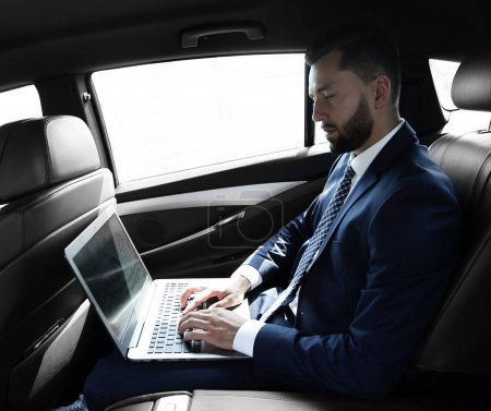 businessman using a laptop in the backseat of a car